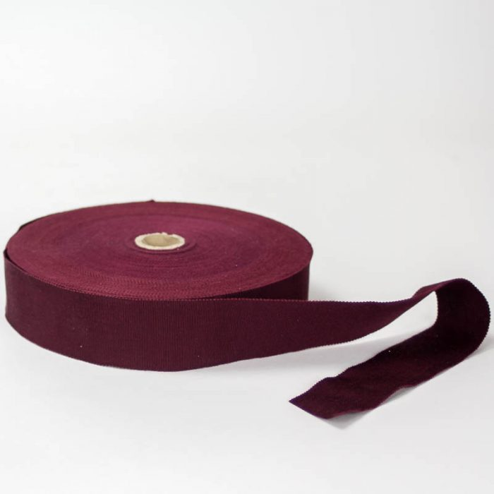 Burgundy. Made in France. Blend of 44% rayon/ 56% cotton grosgrain belting with a saw-tooth edge.