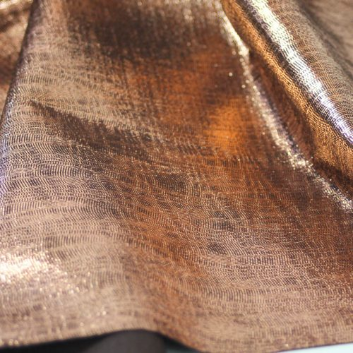 Metallic copper on espresso brown pig suede. 2-1/2 sq ft. Supple and soft leather, thickness of .50-.55mm, and blockable.